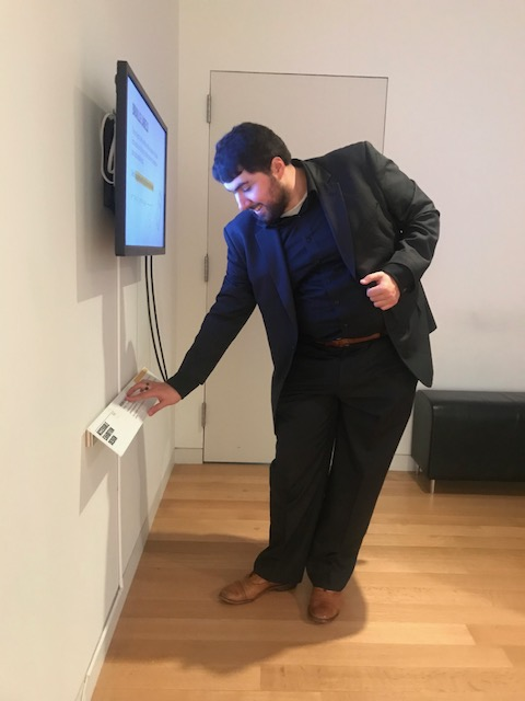 Sina stands in front of a video screen in a gallery bending over slightly to read the braille on a label mounted on an angle coming off the wall.