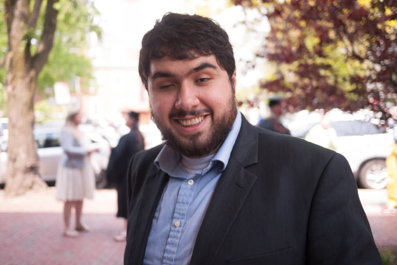 Sina Bahram, a bearded light-skinned man with dark hair smiles brightly to us on a sunny day