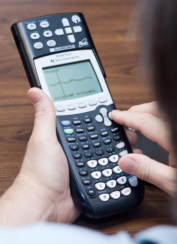 An over-the-shoulder view of a person holding a large calculator, entering in information.