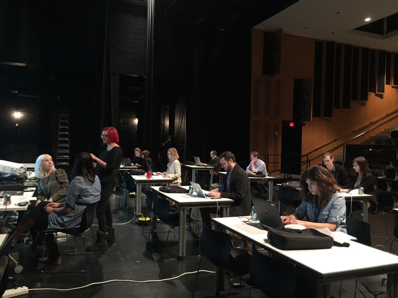 In a dramatically lit space, people sit at three rows of tables that are covered in laptops; some people are working in groups. In the first row, two women turn to a red-headed woman standing, engaging them in conversation.