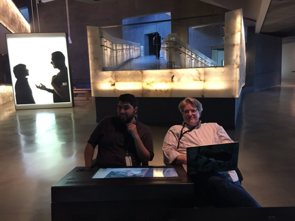 Two men sit at a table in a dimly lit space in front of a projection and a large, illuminated ramp.