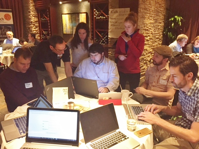 A small crowd hovers behind and around Sina coding at table, illuminated by his laptop screen.