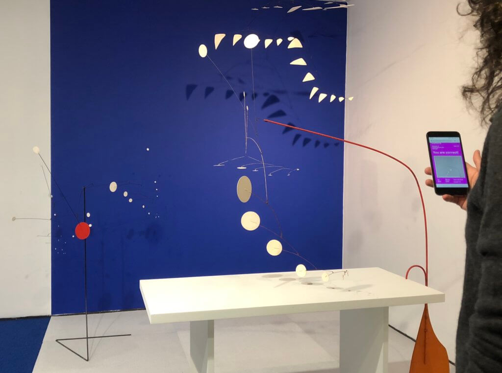 A grouping of Alexander Calder's mobiles and stabiles is depicted. On the right side of the image, a curly haired person, who is mostly cut off from the image, holds a phone up in front of the works.