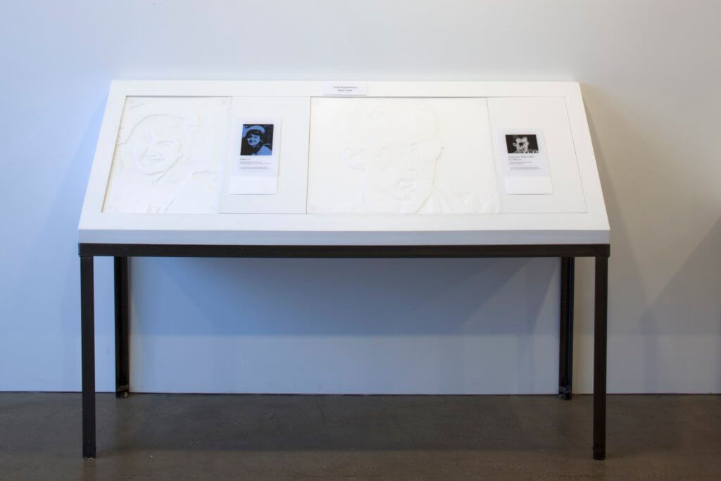 Two tactile images of Andy Warhol paintings are displayed on a table with braille descriptions, tilted slightly back to ease the user when they touch the image.