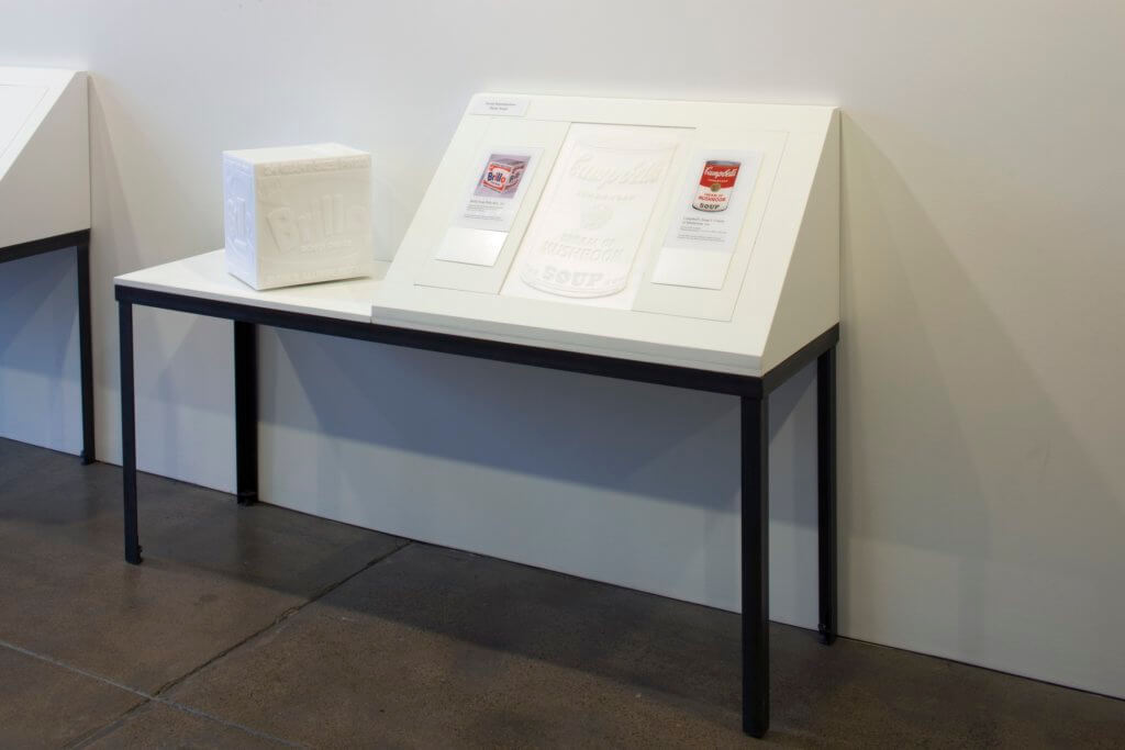A tactile replica of a Brillo Soap Pads Box sits on a table next to an angled display featuring a tactile reproduction of a Campbell's Soup can and small prints of the artworks.