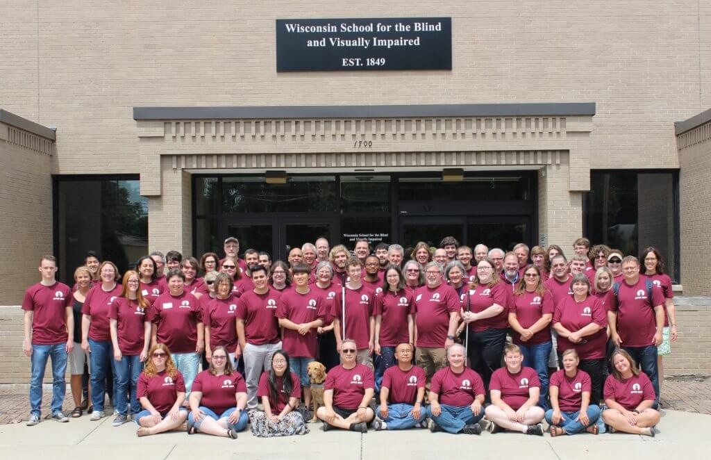 A group of 70 people in maroon shirts pose in front of the entrance of WSBVI.