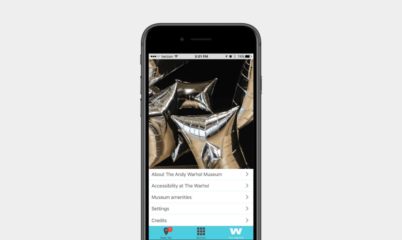 Half of a mobile phone screen features an image of reflective silver square balloons; the lower half lists 5 menu options: About the Andy Warhol Museum, Accessibility at the Warhol, Museum Amenities, Settings, and Credits.