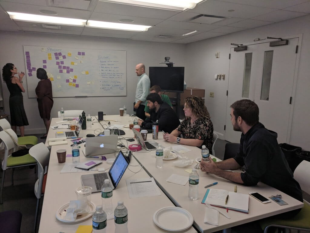 Sina and 2 other people sit around a group of 4 tables pushed together in meeting room. They look at white board where 3 other people stand reviewing post-its that cover the board. Laptops, notebooks, and coffee cups cover the surface of the tables.