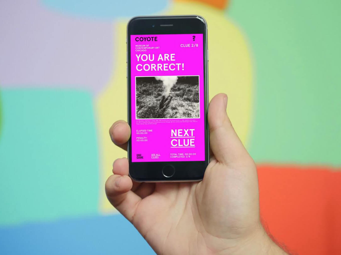 "A light-skinned hand holds up a smartphone with the screen facing you. The screen reads, ""YOU ARE CORRECT!"" at the top and ""NEXT CLUE"" in the bottom right-hand corner."